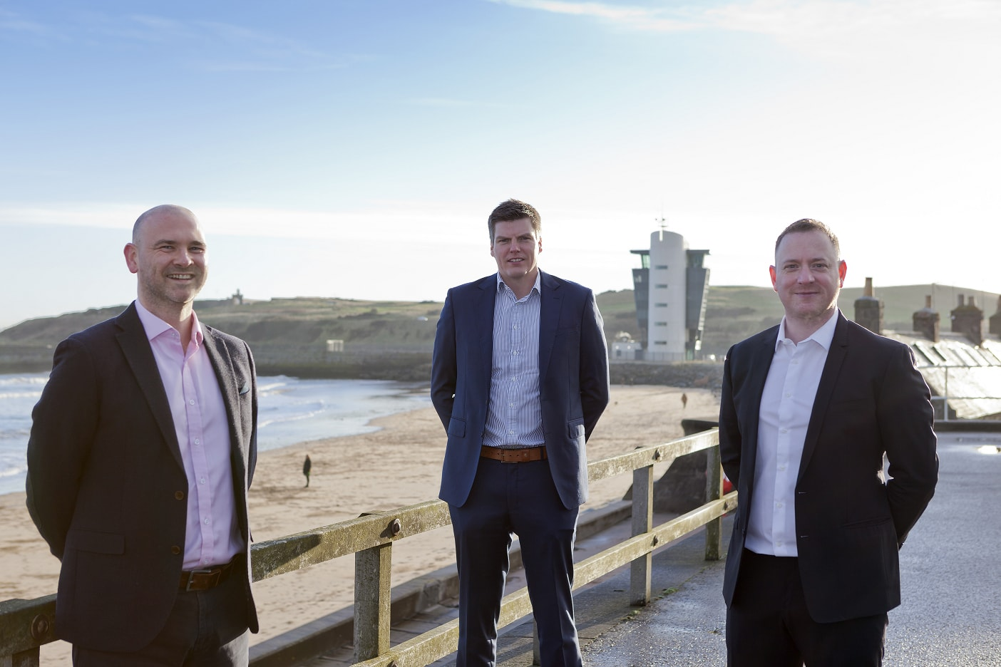 Three businessmen pose together at the beach